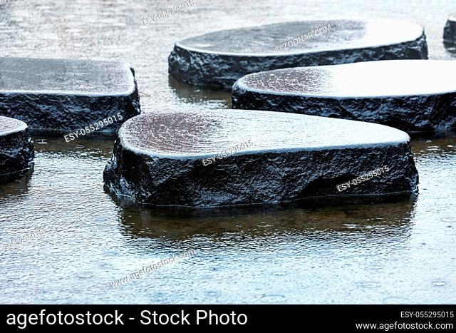 wet stones in the rain in the pond