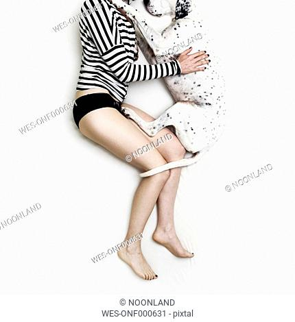 Woman and Dalmatian mongrel lying on white bed sheet