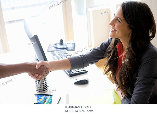 Business people shaking hands at desk in office