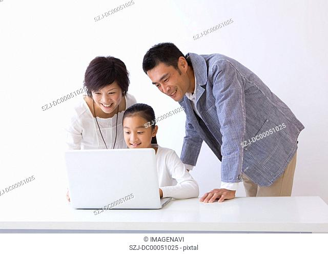 Girl and parents using a laptop