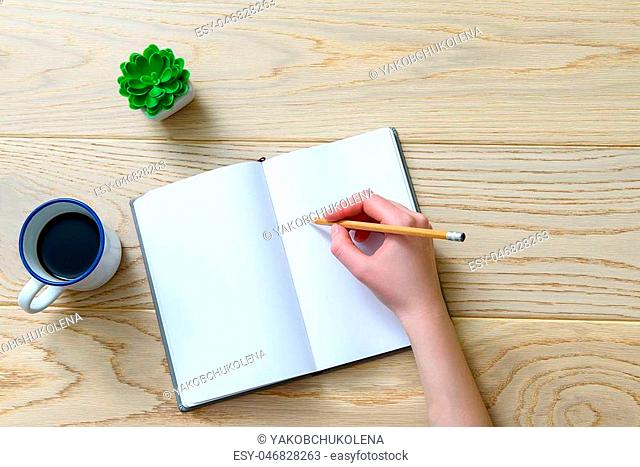 Close up of female hand holding pencil. Cup with dark beverage is nearby open notebook. Top view