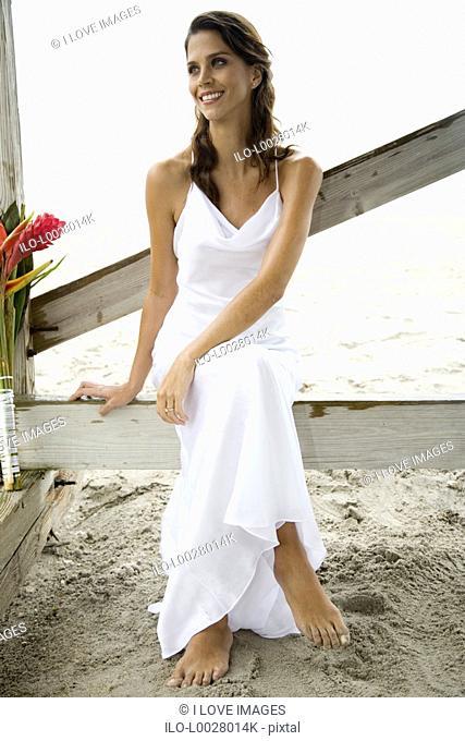A bride sitting on a beach