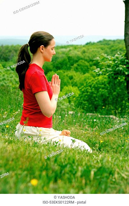 Woman meditating in grassy field
