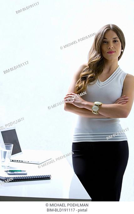 Mixed race businesswoman standing at desk