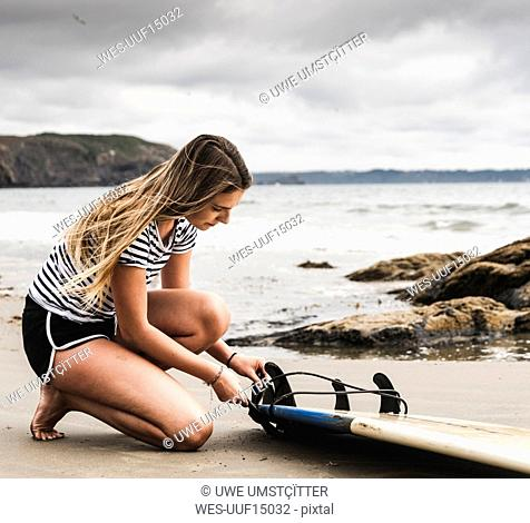 Young woman at the beach preparing surfboard