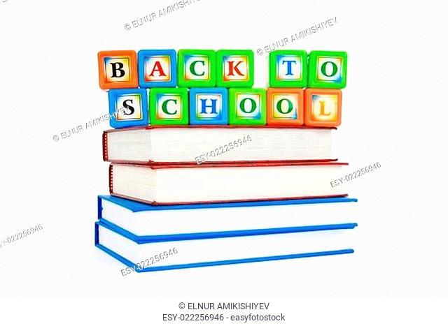 Books and alphabet blocks isolated on white
