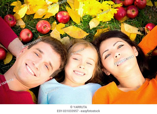 Happy family having fun outdoors in autumn park. Top view portrait
