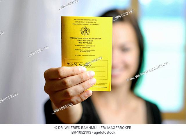 Young woman holding her vaccination card into the camera