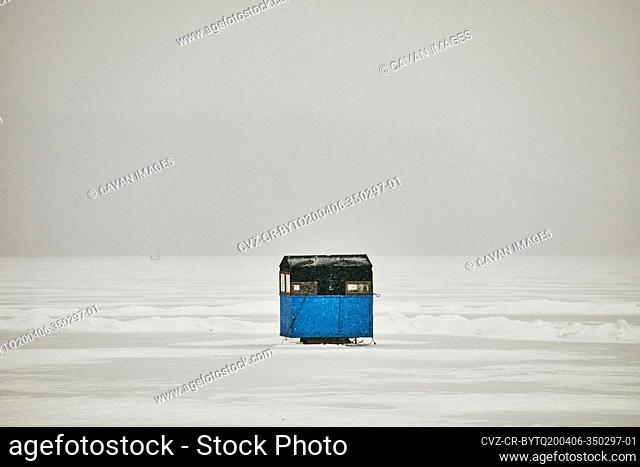 Ice Fishing Shanty on Frozen Lake in Snow Storm