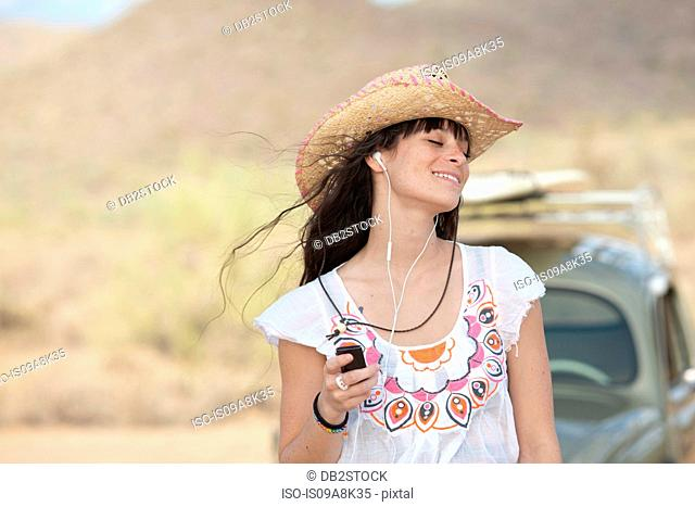 Young woman in cowboy hat wearing earphones, smiling