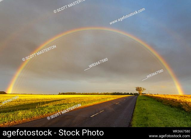 Double rainbow arching over empty countryside highway