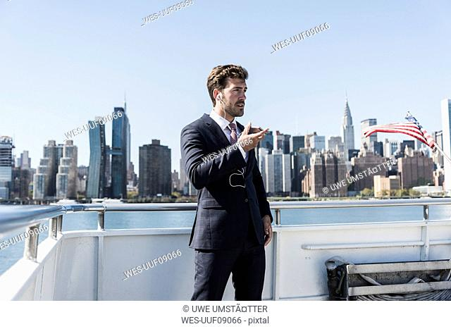 USA, New York City, businessman telephoning on ferry on East River