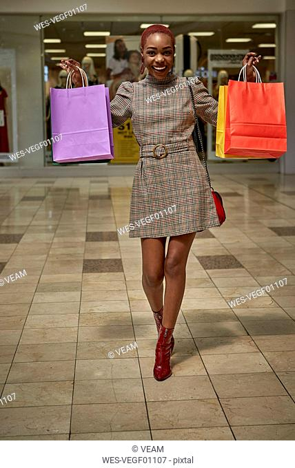 Happy young woman holding colorful shopping bags walking outside a shop