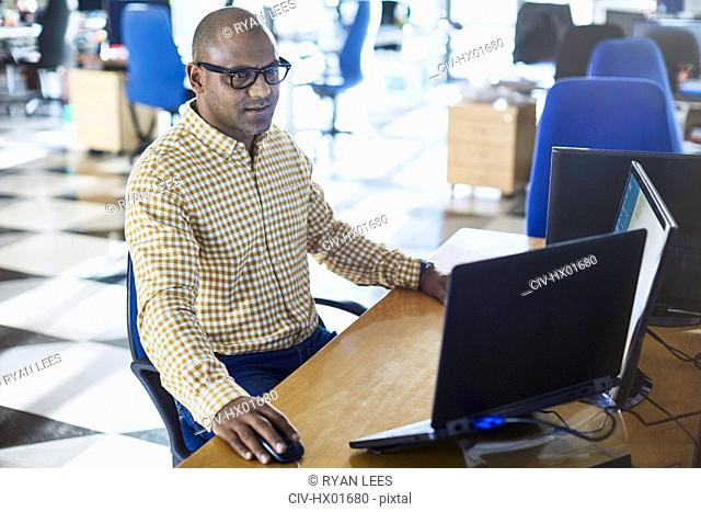Businessman working at laptop and computer in office