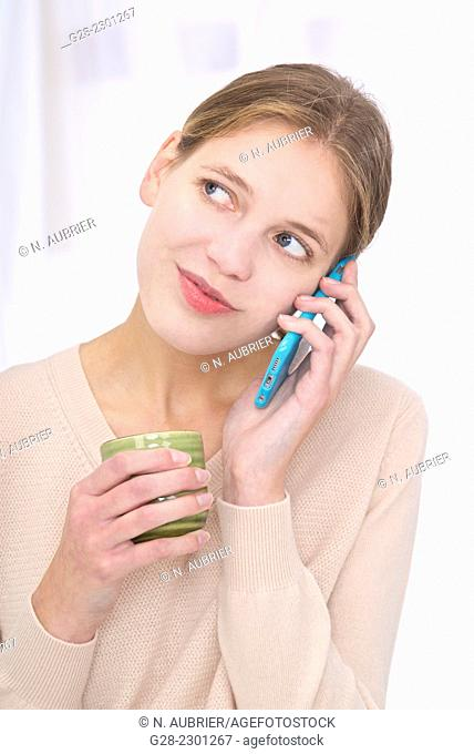 Young woman using an I-phone and holding a green mug in her hand