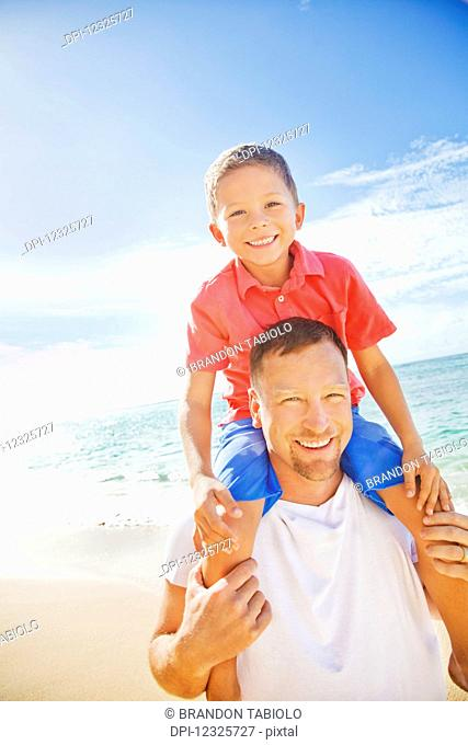 A father and son spending time on a tropical beach on vacation; Honolulu, Oahu, Hawaii, United States of America