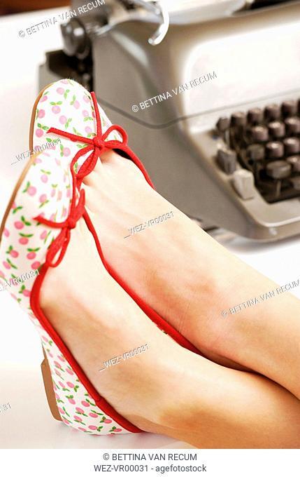 Woman`s feet on desk, close-up