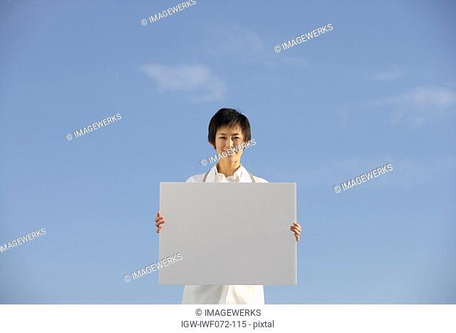 Japan, Honshu, Tokyo, Female doctor holding blank placard, smiling, portrait