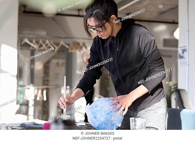 Woman painting balloon