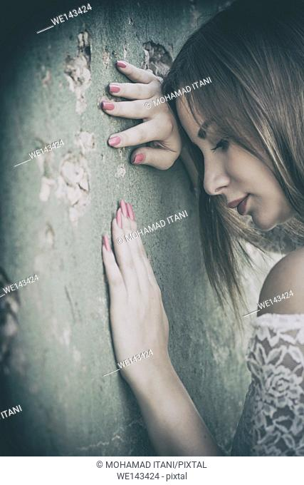 Sad woman leaning against the wall outdoors