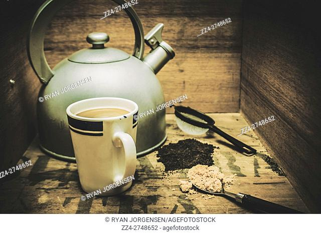Retro vintage toned tea still life in an old tea packing crate with mug of fresh brew, old domed kettle, strainer, dried tea leaves and caramelized sugar in a...