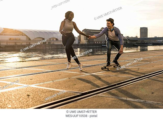 Young couple skateboarding at the riverside