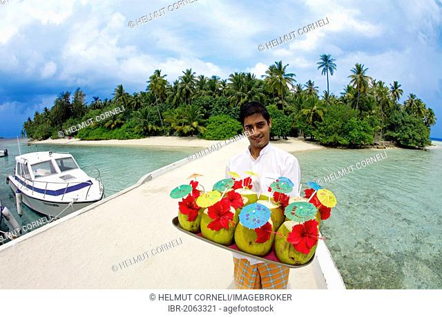 Maldivian serving welcome drinks for new arrivals at the pier, Biyadhoo Island, South Male Atoll, Maldives, Indian Ocean, Asia
