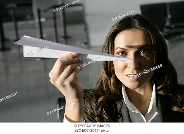 Young businesswoman holding paper airplane in airport