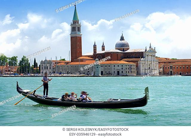 Tourists riding in gondola on Grand canal near San Giorgio Maggiore in Venice, Italy