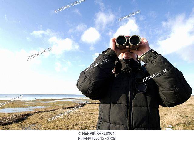 Scandinavia, Sweden, Oland, Girl 8-9 looking through binoculars