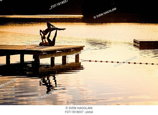 Women practicing acro yoga on lakeside dock at dusk