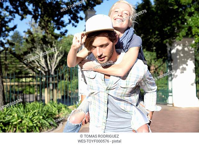 Young man carrying girlfriend piggyback