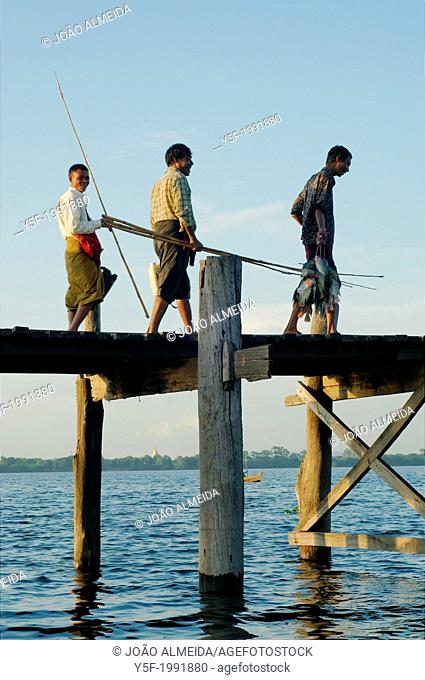 People crossing U Bein bridge at the end of the day