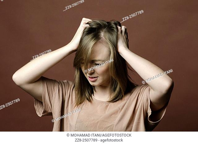 Young woman scratching itchy scalp