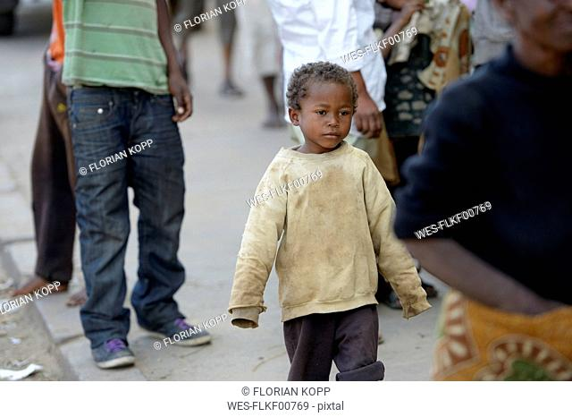 Madagaskar, Fianarantsoa, Homeless boy walking in the street