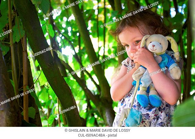 Portrait of female toddler with cuddly toy in woods