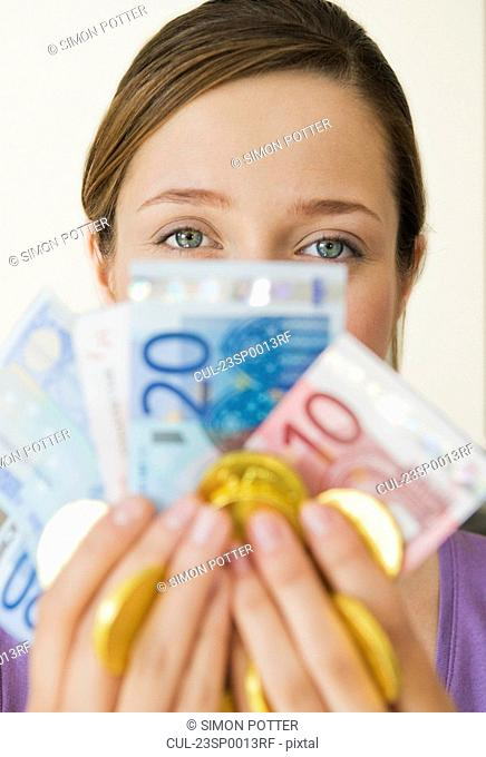 Portrait of woman holding up money