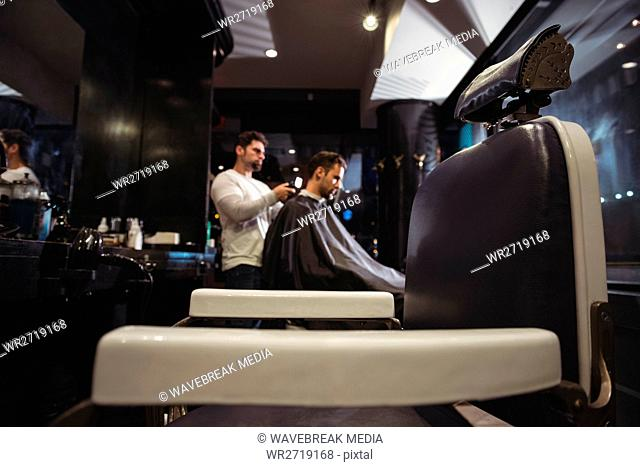 Barber blow drying clients hair