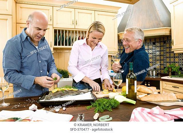 Friends preparing a fish dish together