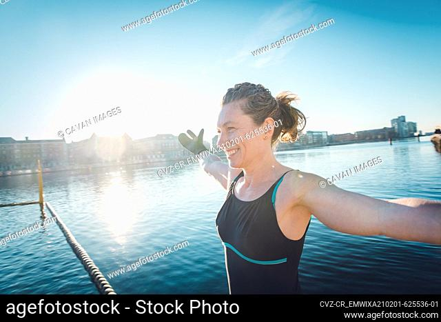 Mature Woman With Arms Outstretched Before Cold Swim in Denmark
