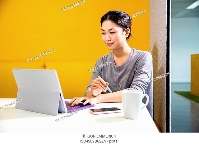Female digital designer at office desk using laptop
