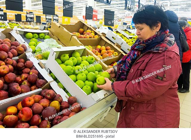 Caucasian woman examining apples