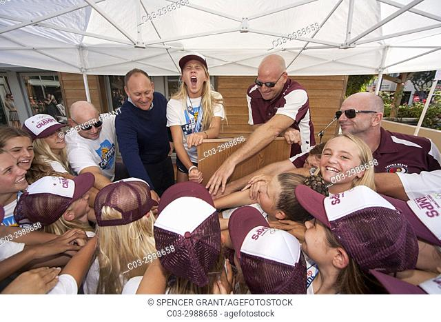 Lead by their captain and coach, a champion girls water polo team celebrates their award ceremony with a cheer in Laguna Beach, CA
