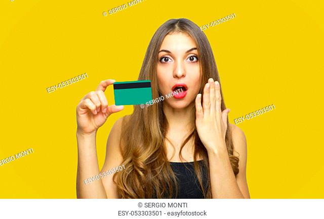 Image of surprised young lady standing over yellow background and holding debit card in hands. Looking at camera