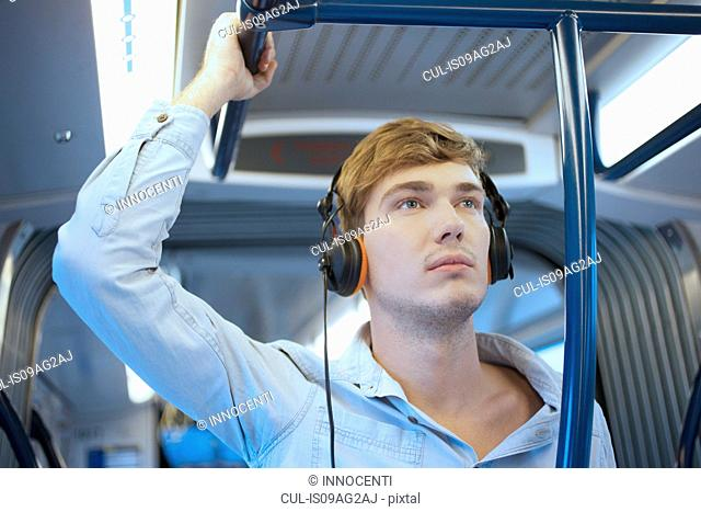 Young man in train carriage listening to headphones