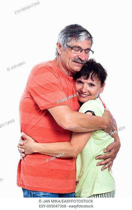 Portrait of happy middle aged couple hugging, isolated on white background