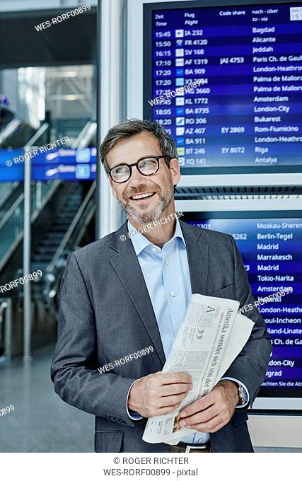 Smiling businessman with newspaper at timetable at the airport
