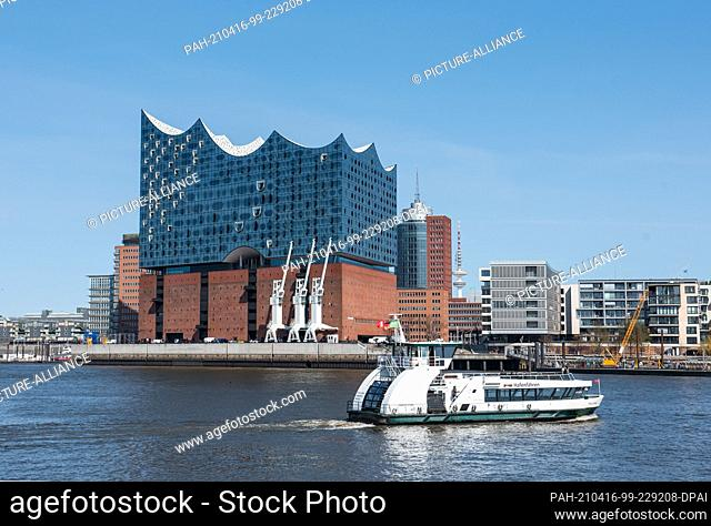 16 April 2021, Hamburg: A harbour ferry is underway on the Elbe in front of the Elbphilharmonie under blue skies and sunshine