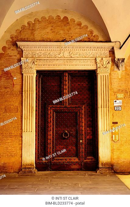 Ornate door with knocker in Bologna, Emilia-Romagna, Italy