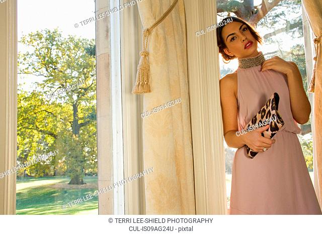 Portrait of glamorous young woman leaning against garden window